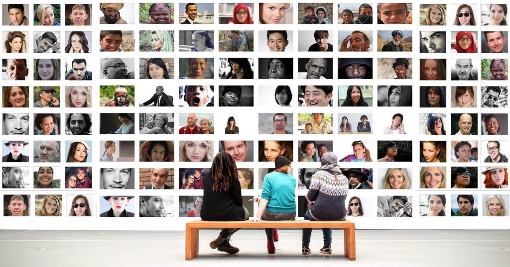 Kuvituskuva, jossa kolme ihmistä galleriassa katsomassa kuvaseinää, joka täynnä erilaisia ihmiskasvoja