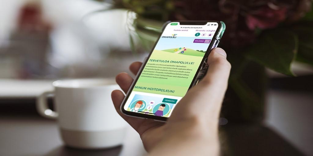 Käsi, jossa on älypuhelin ja siinä Terveyskylä-sovelluksen aloitussivu