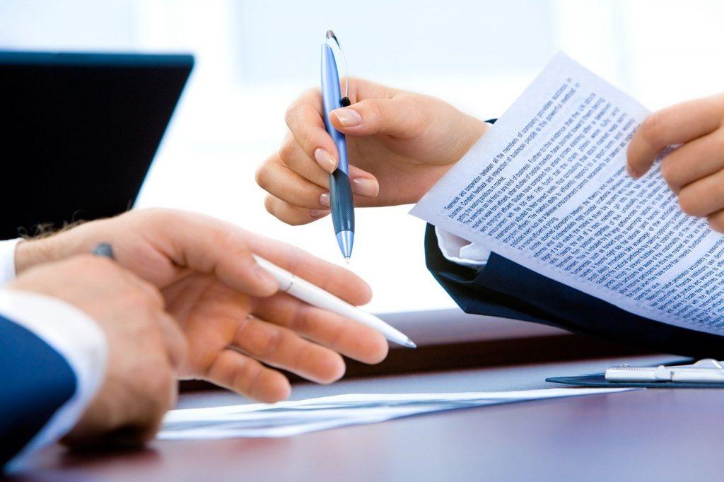 Kaksi henkilöä tarkastelee papereita. Kuvassa näkyvät heidän kätensä, papereita ja kyniä.