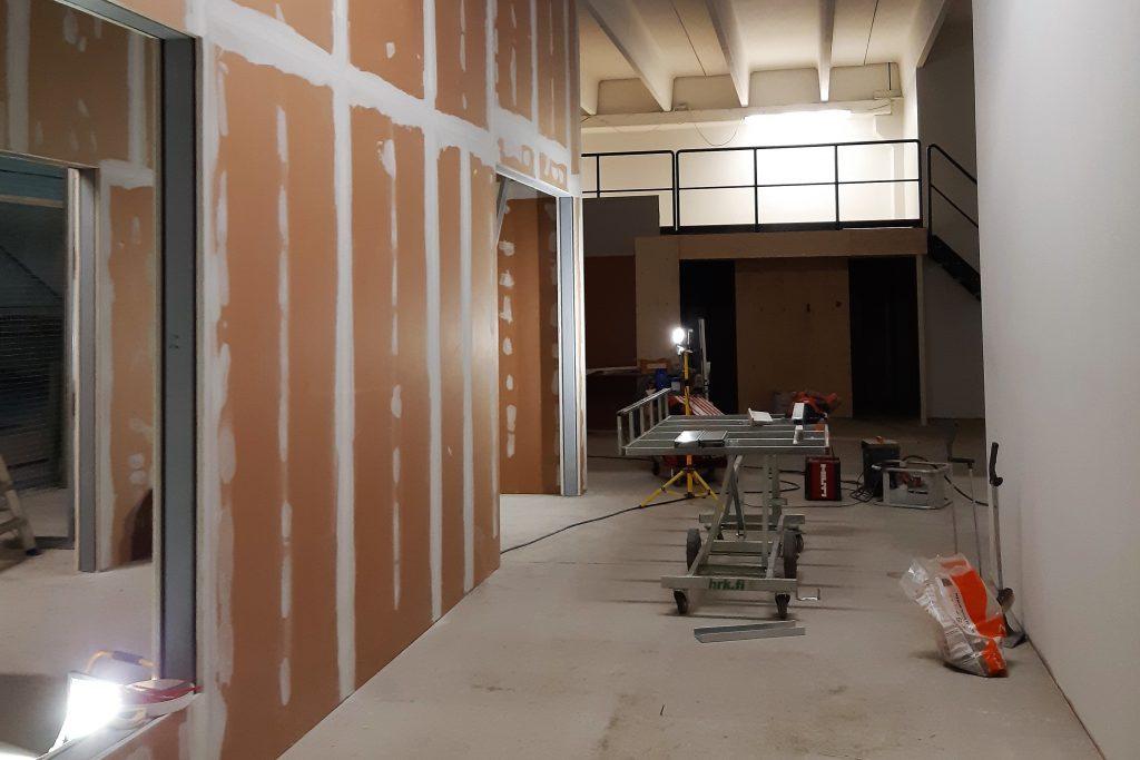 Rakennustyömaa sisätiloissa. Paikalla on rakennustelineitä ja työmaavalaistusta, ja osa seinistä on vielä maalaamatta.