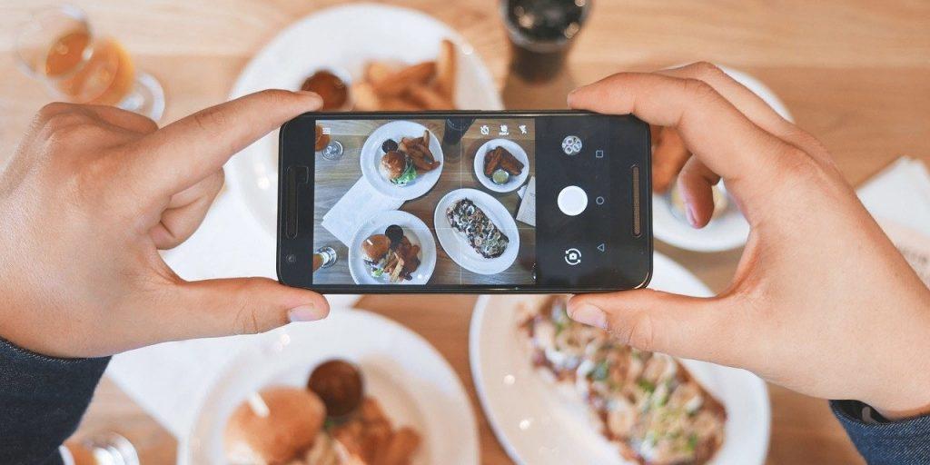 Kuvassa kädet, joissa kamera, jolla otetaan kuvaa ruokapöydällä olevista ruoka-annoksista.