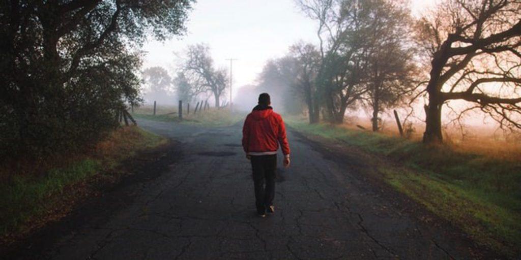 Kuvituskuva. Mies kävelee tietä pitkin eteenpäin. Taustalla sumuinen maisema.