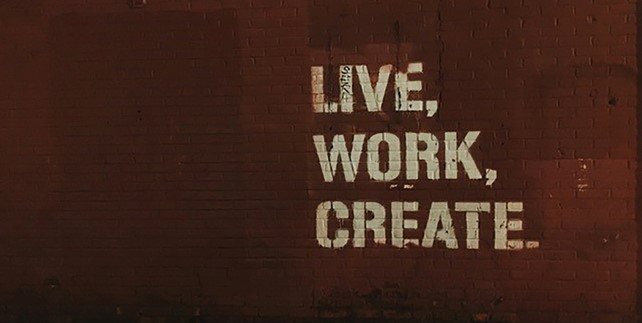"""Red brick wall with quote """"Live, Work, Create""""."""
