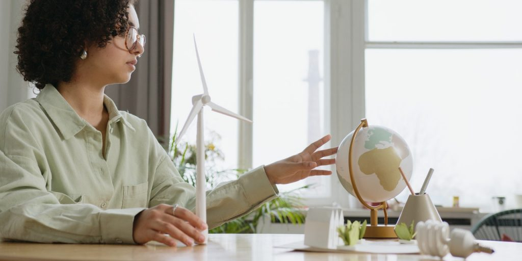 A woman by a table with a globe and windmill model in hands.