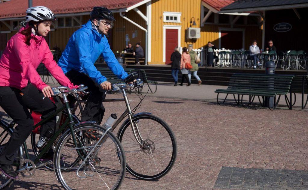[Mies ja nainen ajavat pyörillä kesäisenä päivänä kahvila-alueen edessä.]