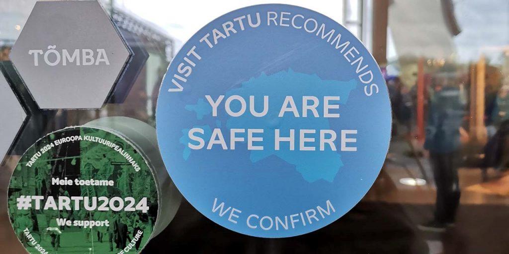[alt text Tapahtumapaikan ovessa oleva tarra jossa teksti: Visit Tartu recomends, You are safe here. We confirm. ]
