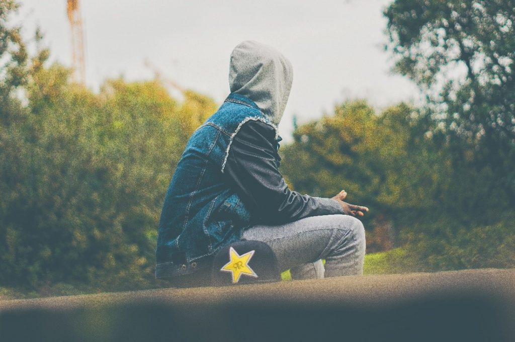 [huppariin pukeutunut nuori mies istuu yksinään puistossa.]