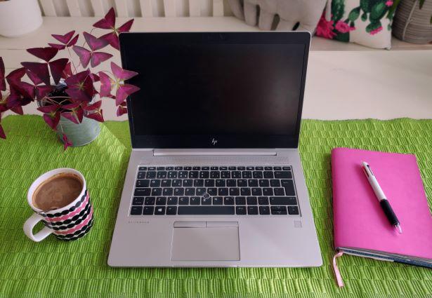 [alt-teksti: Kannettava tietokone, muistivihko ja kahvikuppi.]