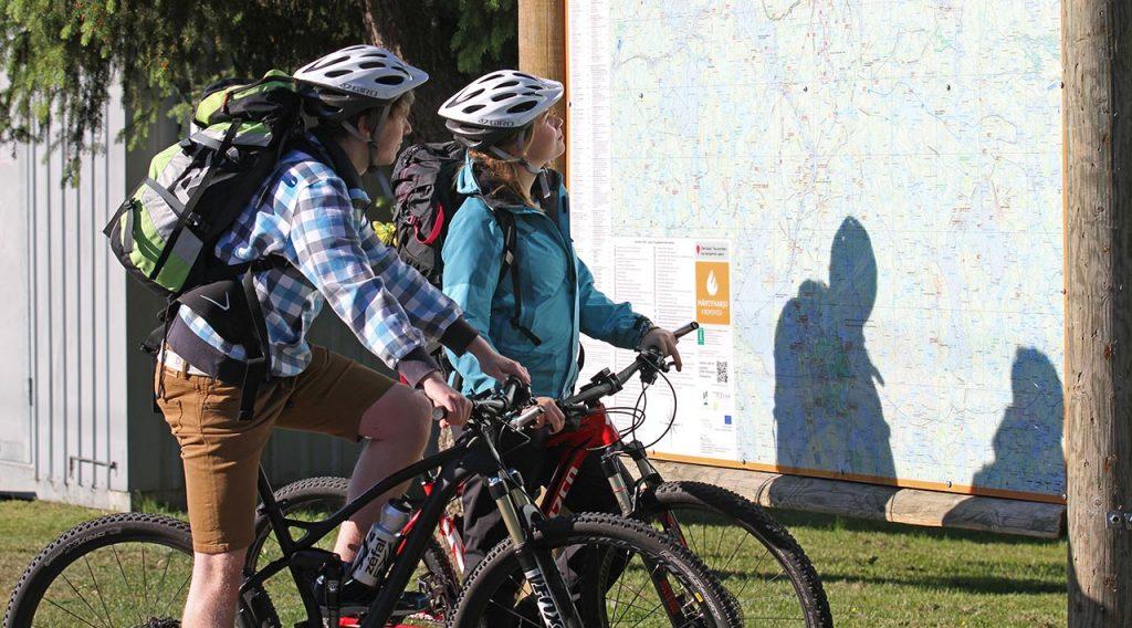 [Alt-teksti: Kaksi pyöräilijää seisoo pyöriensä kanssa suuren opastekarttataulun edessä.]