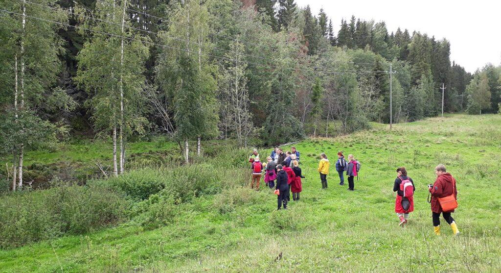 [Alt-teksti: Luontomatkailijoita ja opiskelijoita, noin viisitoista henkilöä, metsäisessä ja kesäisessä maisemassa.]