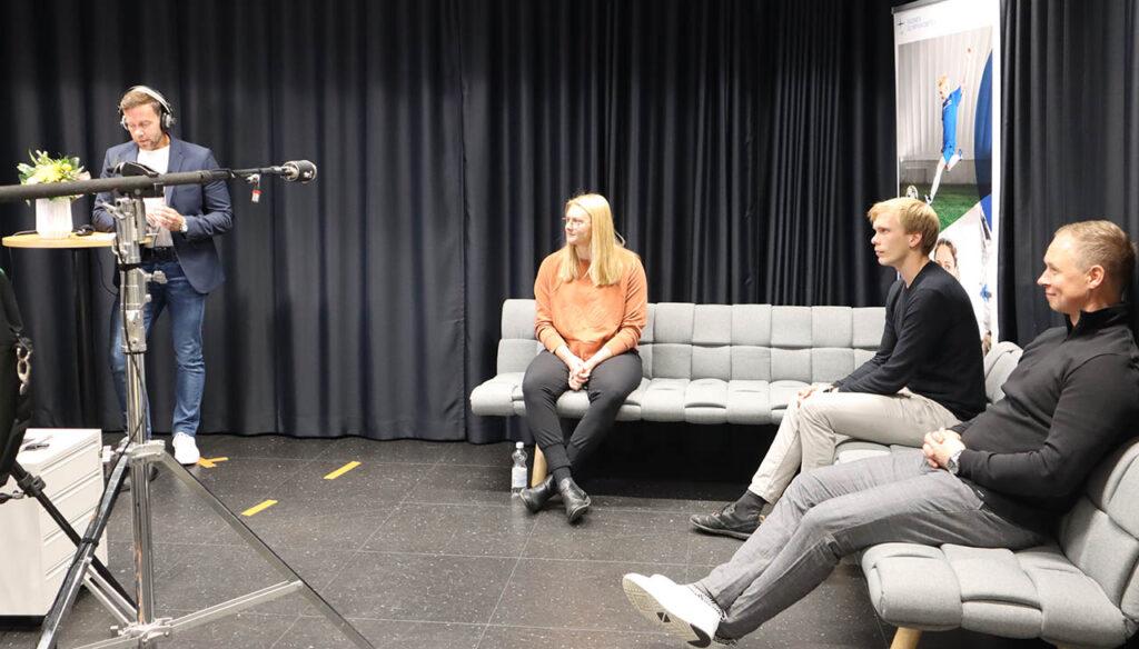 [Alt-teksti: Urheilupanelistit istuvat studion sohvalla. Vasemmalla seisoo tilaisuuden juontaja. Sohvalla istuvat Jenni Kangas, Henrik Mustonen ja Tommi Niemelä.]