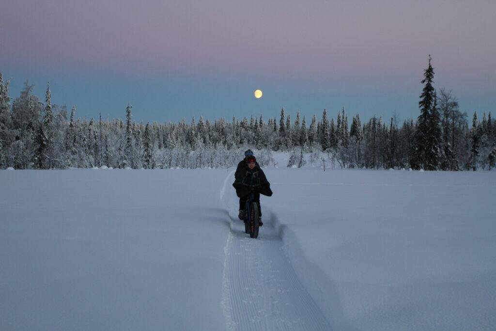 [Alt-teksti: Kaksi pyöräilijää ajaa keskelle lumimaisemaa auratulla pyöräväylällä kuun loistaessa talvisessa hämärässä.]