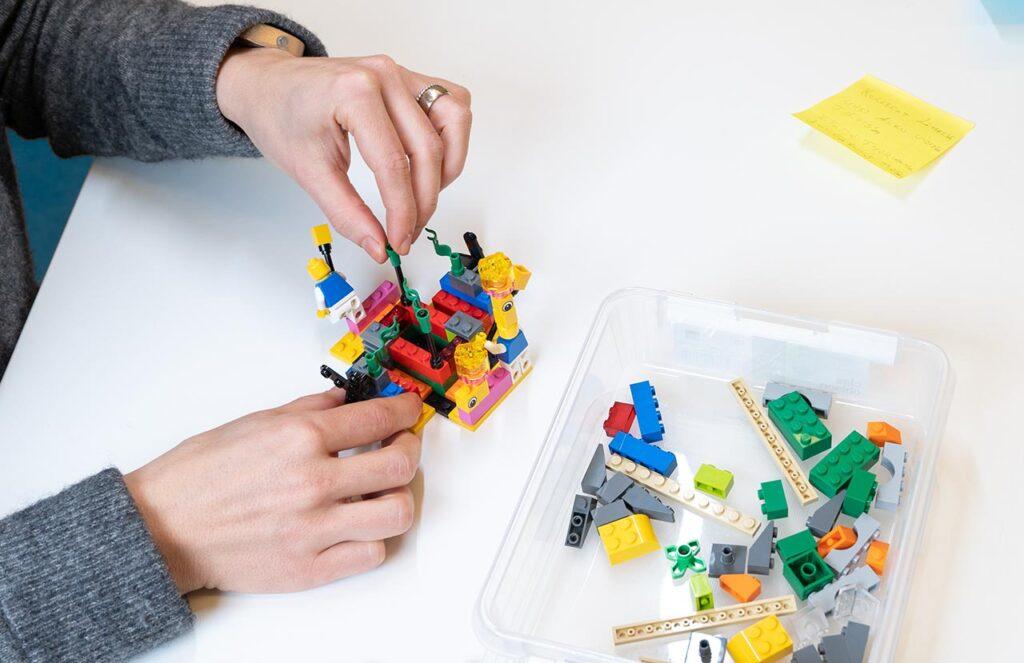 [Alt-teksti: Aikuisen kädet rakentavat pöydällä legopalikoista pientä, mutta monimutkaista rakennelmaa.]