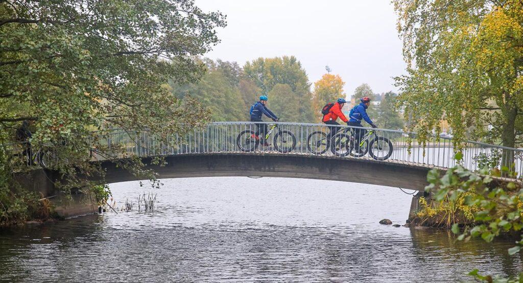 [Alt-teksti: Kaunis kaarisilta vie yli vehmasrantaisen järven kapean kohdan, ja sillalla ajaa kolme pyöräilijää.]