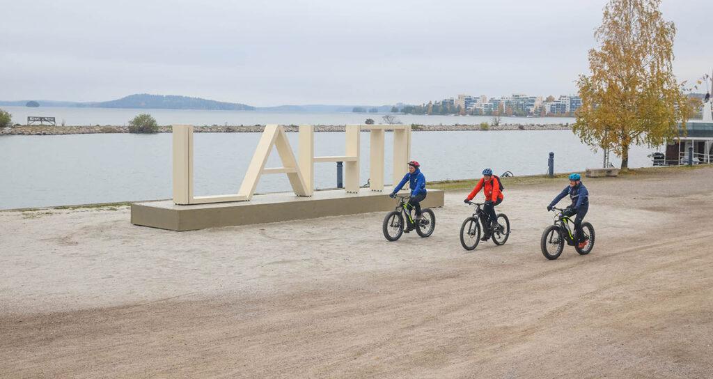 [Alt-teksti: Lahden satamassa oleva veistos, jossa on korkeat kirjaimet LAHTI, ja kolme pyöräilijää ajaa juuri veistoksen editse.]