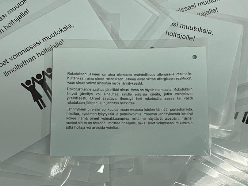 [Alt-teksti: Painettuja mustavalkoisia lehtisiä, jotka sisältävät tietoa rokotuksen jälkeisestä tilanteesta. Esite muun muassa kuvailee, miten jännityksen oireet saattavat ilmetä.]