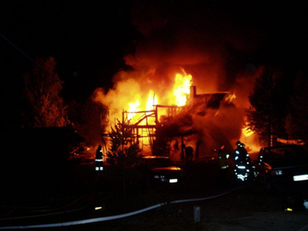 [Alt-teksti: Täysin liekeissä oleva asuinrakennus ja sen luona palomiehiä sammuttamassa tulipaloa.]